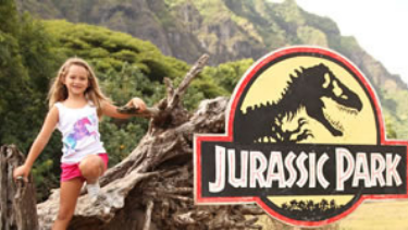 Girl standing in front of jurassic park sign in kualoa ranch