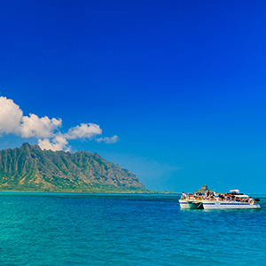 boat-off-hawaii-coast-clear-water-mountains