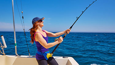 woman-deep-sea-fishing-boat-blue-water
