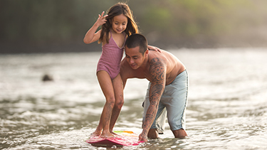 man-teaching-girl-to-surf-hawaii