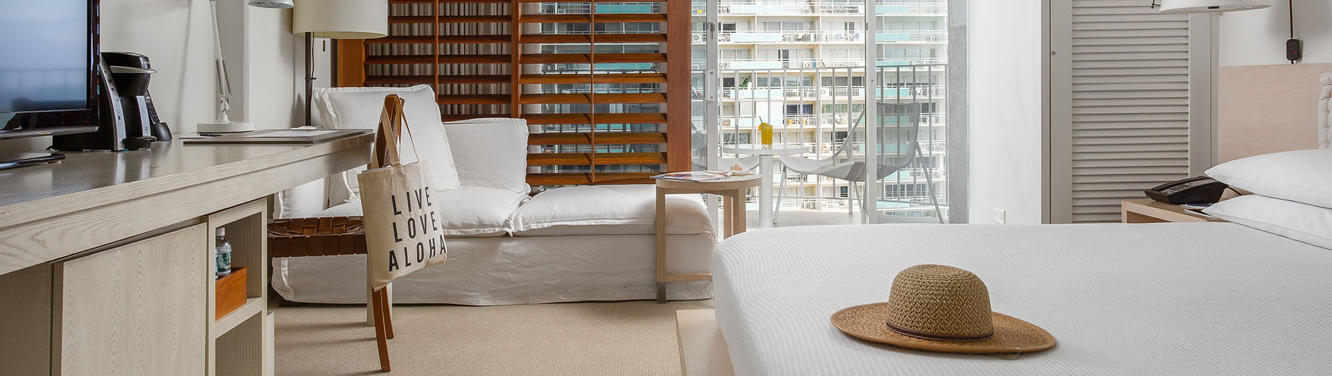 Brightly lit modern hotel room with king bed, desk, chaise lounge and private balcony overlooking Waikiki Beach and ocean
