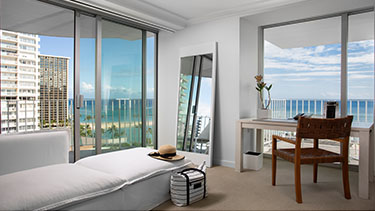 Large white hotel living room with couch, desk and tv and views of Honolulu ocean from oversized window