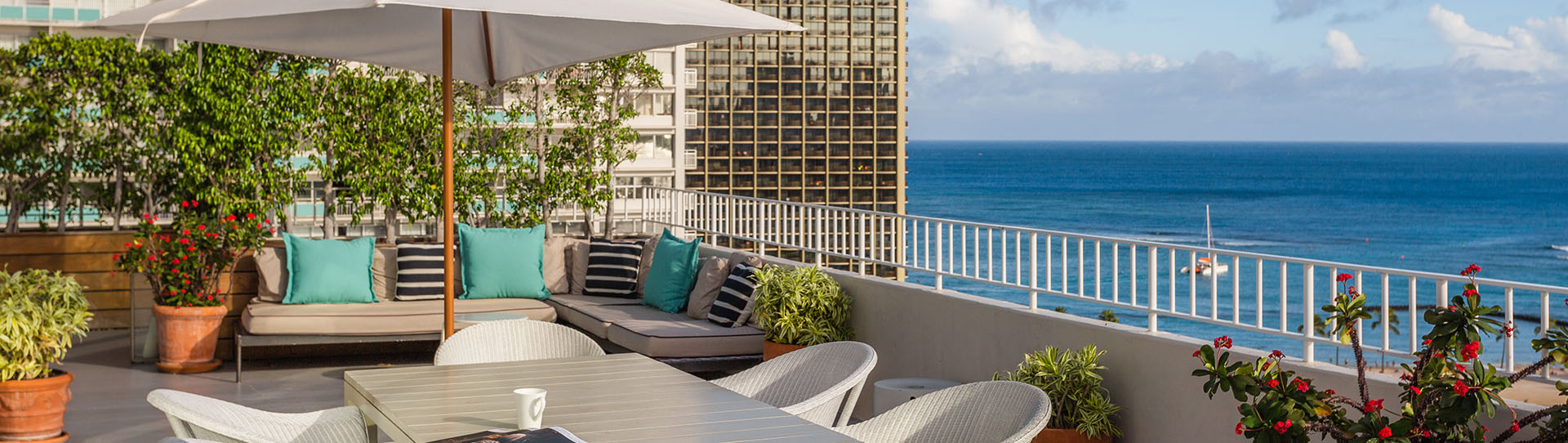 Resort penthouse balcony with trendy corner couch and dining table overlooking blue waters of Waikiki Beach