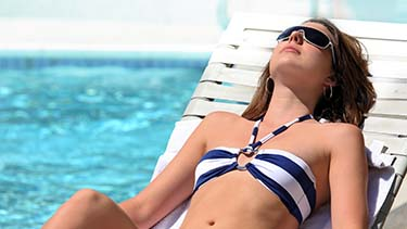 Woman sunbathing poolside on white lounge chair